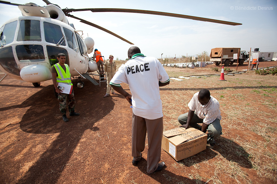 11 december 2010 - Riwoto, South Sudan - Training officers for the Southern Sudan Referendum Commission check completed registration materials next to a UNMIS helicopter in Riwoto, Eastern Equatoria State, South Sudan. The UNMIS retrieves completed registration materials in Riwoto - Kapoeta North County, the day after registration for South Sudan's referendum closed. The referendum is scheduled to take place on January 9, 2010. Photo credit: Benedicte Desrus