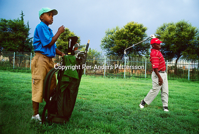 SOWETO, SOUTH AFRICA - MARCH 28: An unidentified man plays golf with a young boy as caddie on March 28, 2005 at the Soweto Country Club in Soweto outside Johannesburg, SA. A growing number of people belong to the new black elite in the country. Well educated and connected, they have risen from the poverty in the townships to a very different lifestyle, since the fall of Apartheid and the start of democracy in the country in 1994..(Photo by Per-Anders Pettersson/Getty Images)