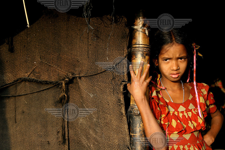 A girl living in a Dhaka slum leans on a pole that supports a slum dwelling made of hessian sacks.