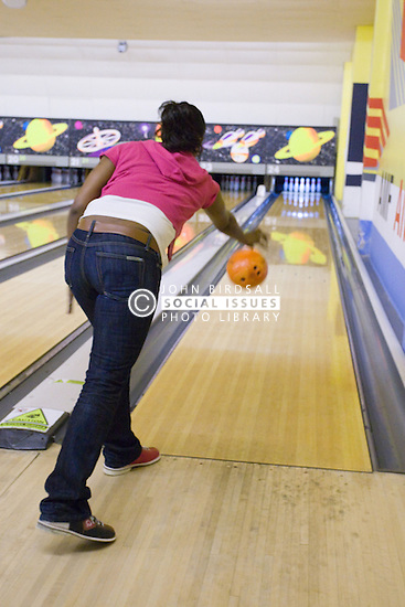 Young woman bowling a ball down an indoor ten pin bowling alley,