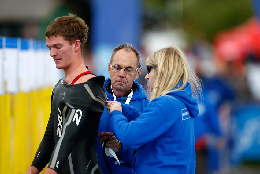 Photo: Richard Lane/Richard Lane Photography. GE Parc Bryn Bach Triathlon. 19/09/2010. Officials help a competitor with a out of his wet suit after the zip jams in transition during the Elite Mens' race.