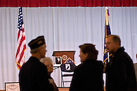 The podium with plaque, flag, and a photo of President Bush, a bell and a chair with a POW-MIA flag sits on the stage during an open house for the Young-Budd Post 171 of the American Legion new home on East College Street. Photo Copyright Gary Gardiner. Not be used without written permission detailing exact usage.