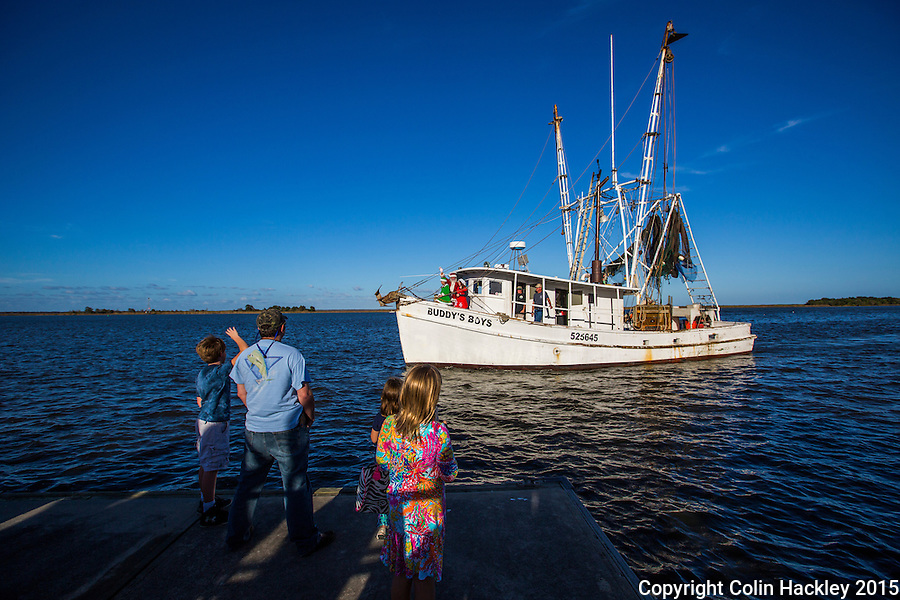 Santa does have a sleigh, but in Apalachicola, Fla. he arrives by shrimp boat on the day after Thanksgiving. Here visitors crowd the docks on Water Street to watch him arrive on the boat Buddy's Boys.<br /> <br /> COLIN HACKLEY PHOTO