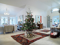The Christmas tree is placed in all its splendour in the centre of this open-plan living/dining room