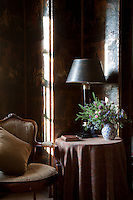 An antique screen stands behind a chair and table in a corner of the billiard room