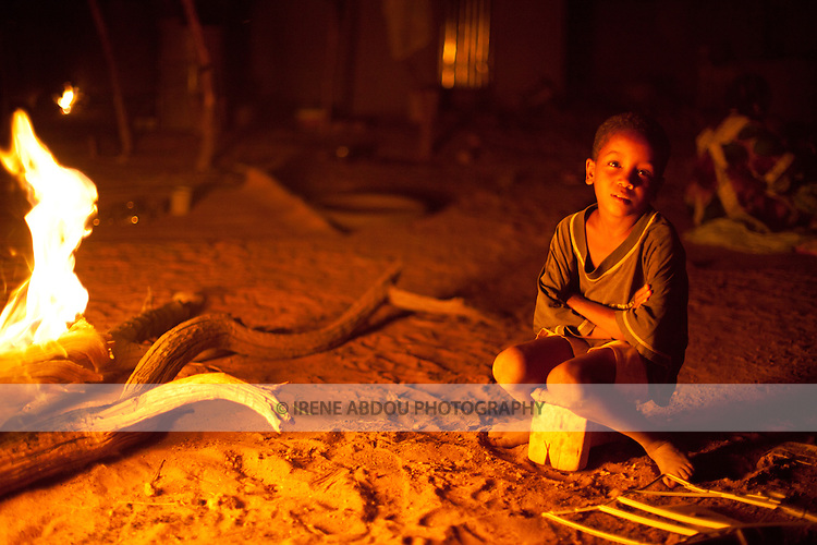 A boy sits next to the Tabaski fire.  Tabaski (Eid-Al-Adha) is Muslim West Africa's largest holiday and is celebrated with the biggest feast of the year.  Traditionally, each family slaughters one or more goats or sheep, which are roasted whole by the fire throughout the day.  Among this family in Djibo in northern Burkina Faso, the men got a late start to the barbecue, and the meat continues roasting into the night.