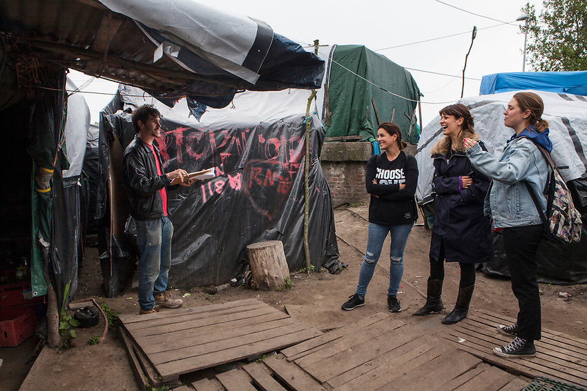 "Jack Steadman, who is taking a census of the camp talks to (left to right) Dani Lawrence, Liana Bird and Josie Naughton who are the main figures of Help Refugees UK.  Photographed in ""The Jungle"" refugee camp in Calais France. Help Refugees has grown out of #helpcalais, a social media campaign started by Lliana Bird (Radio X DJ), Dawn O'Porter (Writer and Presenter), Josie Naughton and Heydon Prowse (The Revolution will be Televised) to raise a few funds and collect goods to take to Calais to help in some small way. The public response to the campaign was huge, and we were quickly able to provide aid in Calais and far beyond. Dani Lawrence' involvement begin when she filled a car with supplies and donations and drove to Calais."