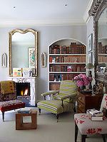 An armchair upholstered in a bright stripe beside an 18th century French mirror above the limestone fireplace is the focal point of the library
