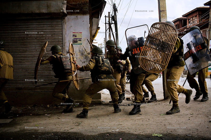 The Jammu & Kashmir police charge down a narrow lane as they clash head-on with separatists less than a hundred feet away in Srinagar, Kashmir, India. Photo by Suzanne Lee