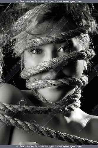 Artistic portrait of a young beautiful woman with her face tied in ropes