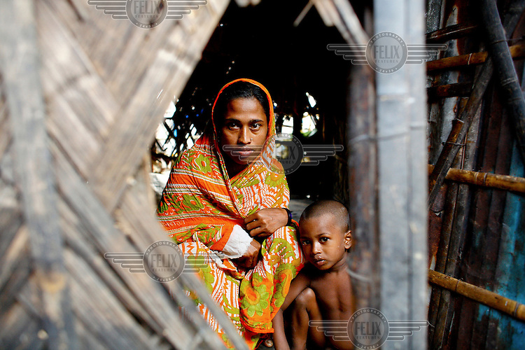 A woman and her son look out from their home in one of the city's slum districts. It is thought that more than six million people live in slums in Dhaka.