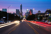 Vivid pink sunset falls on the downtown Austin skyline, view from the middle of the road on South Congress looking north to the Texas State Capitol on a beautiful summer evening - Stock Image.