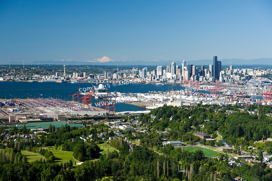 An aerial view of the Port of Seattle, Elliott Bay, and the Seattle skyline on a sunny day.