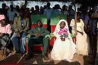MPHANDULA, MALAWI - AUGUST 19: Betino Phipi, age 21, sits with Suzana Nabanda, age 16, his new wife, on August 19, 2006 in Mphandula village, about 30 miles outside Lilongwe, Malawi. Mr. Phipi, a farmer, just got married a few hours earlier and he is showing his wife to the villagers. Mphandula is a poor village in Malawi, without electricity or clean water. Nobody owns a car or a mobile phone. Most people live on farming. About 7000 people live in the village and the chief estimates that there are about five-hundred orphans. Many have been affected by HIV/Aids and many of the children are orphaned. A foundation started by Madonna has decided to build an orphan center in the village through Consol Homes, a Malawi based organization. Raising Malawi is investing about 3 million dollars in the project and Madonna is scheduled to visit the village in October 2006. Malawi is a small landlocked country in Southern Africa without any natural resources. Many people are affected by the Aids epidemic. Malawi is one of the poorest countries in the world and has about 1 million orphaned children. (Photo by Per-Anders Pettersson)