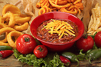 Bowl of chili and cheese with side order offerings of crinkle fries, curly fries and onion rings.
