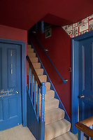 The staircase landing of a Georgian guest house with blue woodwork and red walls and ceiling.