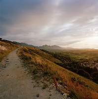 A dirt track overlooking the countryside and village of Llanes, Asturias, Spain