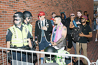 "Alt-right provocateur Milo Yiannopoulos stands behind barricades with police away from counter-protesters after marching in the Straight Pride Parade in Boston, Massachusetts, on Sat., August 31, 2019. Yiannopoulos wore a sequined red hat in the style of Make America Great Again (MAGA) hats reading ""Make America Straight Again."" Yiannopoulos addressed the crowd with a short speech on arrival and then rode the ""Trump Unity Bridge"" float for the duration of the parade. Despite leading the Straight Pride Parade and singing along with patriotic American songs throughout the parade, Yiannopoulos is gay and is not an American citizen."