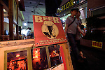 People walk past a sign outside a bar in Shimokitazawa, Setagaya Ward, Tokyo, Japan..Photographer: Robert Gilhooly