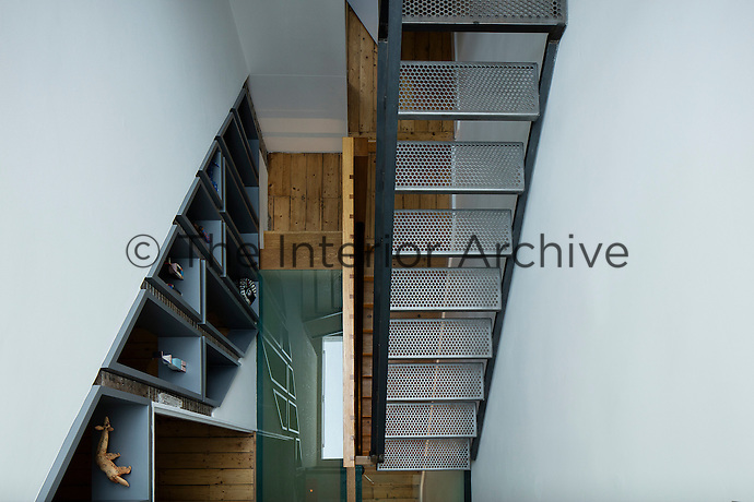 A Victorian home has been given a modernist aesthetic. For storage and display, a shelf begins at the front door and runs like ribbon throughout the house, providing visual continuity between its rooms. The first floor landing was replaced with high-strength glass and the stairs are black steel  with perforated treads, which allow light to filter downward through the house.