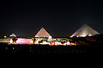 "Giza, Cairo, Egypt -- The three famous pyramids at Giza, surrounded by the ""queen's pyramids"" and with the remains of the funerary temple of Khafre (Khephren) (featuring the Great Sphinx) are spectacularly illuminated during the famous sound and light show at Giza. © Rick Collier / RickCollier.com"