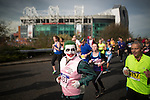 © Joel Goodman - 07973 332324 . 10/04/2016 . Manchester , UK . A racer dressed as The Joker taking part in the 40th Greater Manchester Marathon , passing Manchester United stadium ( Old Trafford ) . Photo credit : Joel Goodman