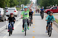 NWA Democrat-Gazette/DAVID GOTTSCHALK  Alyx Ramsey, a third grade teacher at George Elementary School, raises her arms Wednesday, May 10, 2017, as she approaches the school with Estrella Perez-Rivas (left) and Starnie (clo) Leas (right), both fourth grade students, after riding from Shiloh Square to the school in Springdale. Students from the school participated in the second annual Springdale City-Wide Walk and Bike to School Day. The students rode from the square to the school on the Razorback Regional Greenway. Mayor Doug Sprouse read a proclamation before the start of the ride.