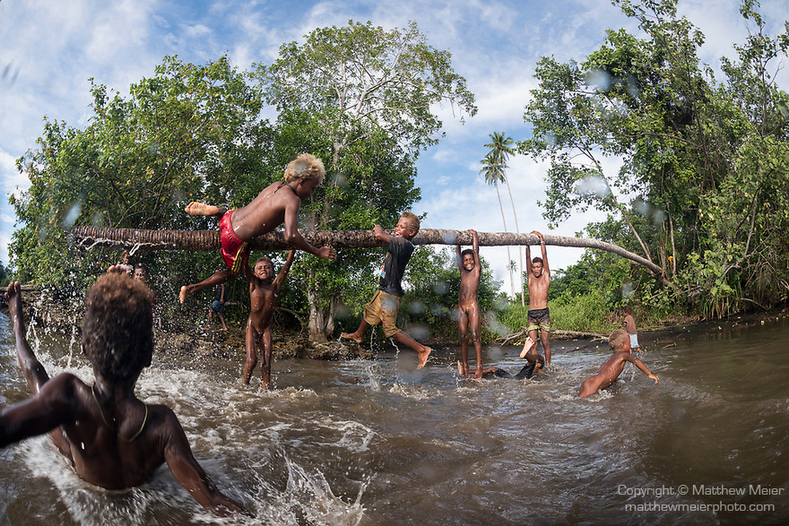 Munda, Western Province, Solomon Islands; local boys from a nearby village playing in the shallow water on the bent tree trunk of a coconut palm and posing for pictures