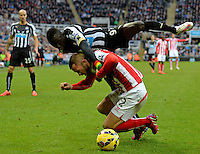Papiss Cisse of Newcastle United gets to grips with Phillip Bardsley of Stoke City