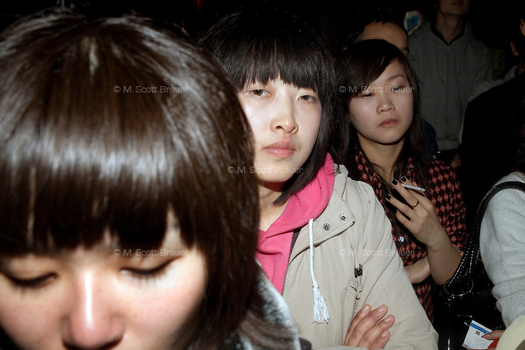 Girls in the audience listen to a punk band perform at Castle Bar in Nanjing, China.