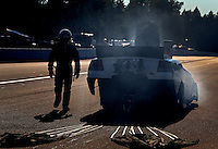 Aug. 1, 2014; Kent, WA, USA; NHRA funny car driver Paul Lee walks away from his smoking car during qualifying for the Northwest Nationals at Pacific Raceways. Mandatory Credit: Mark J. Rebilas-USA TODAY Sports