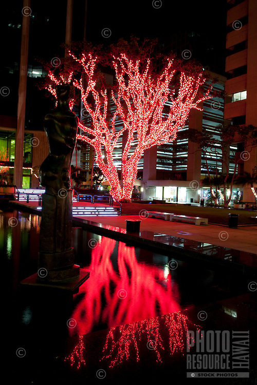 A pond and its adjacent benches reflect the red Christmas lights decorating a tree in Bishop Square, downtown Honolulu, O'ahu.