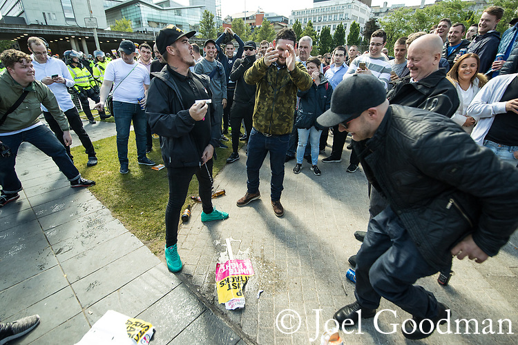 "© Joel Goodman - 07973 332324 . 11/06/2017 . Manchester , UK . A demonstrator urinates on an anti-fascists placard that was grabbed from anti-fascist protesters . Demonstration against Islamic hate , organised by former EDL leader Tommy Robinson's "" UK Against Hate "" and opposed by a counter demonstration of anti-fascist groups . UK Against Hate say their silent march from Piccadilly Train Station to a rally in Piccadilly Gardens in central Manchester is in response to a terrorist attack at an Ariana Grande concert in Manchester , and is on the anniversary of the gun massacre at the Pulse nightclub in Orlando . Photo credit : Joel Goodman"