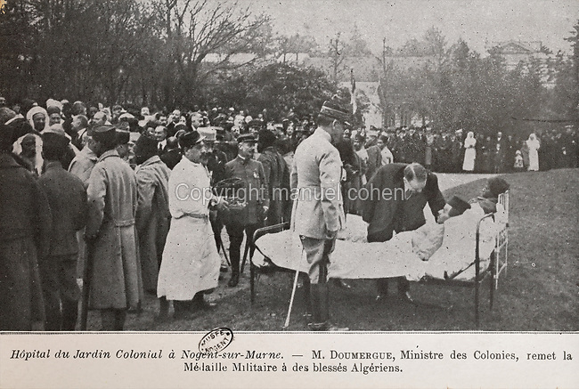 Wounded Algerian soldier receiving a medal from Gaston Doumergue, Minister for Colonies, outside the hospital used during the First World War for treating colonial troops, originally the Cochinchina Pavilion (Cochinchina, now in South Vietnam, was a French colony 1862-1954) in the Jardin d'Agronomie Tropicale, or Garden of Tropical Agronomy, in the Bois de Vincennes in the 12th arrondissement of Paris, postcard from the nearby Musee de Nogent sur Marne, France. During the war the colonial hospital treated over 4800 patients and it closed on 1st May 1919. The garden was first established in 1899 to conduct agronomical experiments on plants of French colonies. In 1907 it was the site of the Colonial Exhibition and many pavilions were built or relocated here. The site is listed as a historic monument. Picture by Manuel Cohen / Musee de Nogent sur Marne