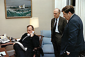 United States President George H.W. Bush, left, speaks on the telephone from the White House in Washington, DC on December 20, 1989 as National Security Advisor Brent Scowcroft, center, and White House Chief of Staff John Sununu, right, look on.<br /> Mandatory Credit: Carol T. Powers / White House via CNP