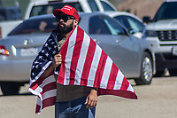 MEXICALI, MEXICO - April 5  A person wrapped in an American flag is seen from the mexican side of the border fence on April 5, 2019 in Mexicali, Mexico.<br /> President Trump on Friday visited Calexico, a small city in a largely agricultural region between Arizona and the Pacific, to inspect an upgraded portion of fencing and to meet with law enforcement. That's more attention than usual for a border town that locals say is defined by its interconnection with Mexico, its infernal summers and its labor-based economy. <br /> (Photo by Luis Boza/VIEWpress)