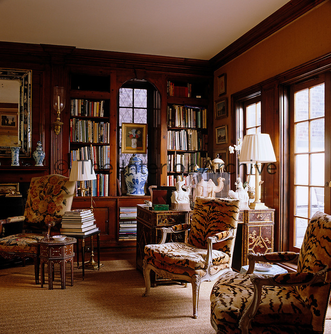 A pair of bergeres upholstered in faux tiger-skin stands by the window in the library-style living room