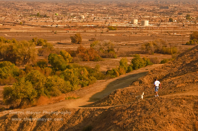 Man walking his dog on the bluffs below Panorama Park, Bakersfield, California.