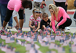 From left, Deborah Alves, Avery Plattsmier, 8, Wyatt Plattsmier, 3, and Megan Cantley participate in the 4th annual Veterans Suicide Awareness March at Western Nevada College, in Carson City, Nev., on Saturday, May 5, 2018. More than 8,000 American flags are planted at the campus to symbolize the number of veteran suicides each year in the U.S. <br /> Photo by Cathleen Allison/Nevada Momentum