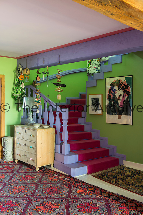 The walls of the entrance hall are painted a lime green offset by the purple painted wooden staircase