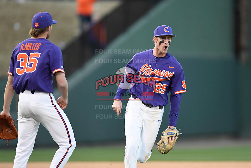Third baseman Patrick Cromwell (25), right, of the Clemson Tigers shouts as he celebrates the final out of a 5-1 win over the South Carolina Gamecocks in the Reedy River Rivalry game on Saturday, March 3, 2018, at Fluor Field at the West End in Greenville, South Carolina. At left is closer Ryan Miller. (Tom Priddy/Four Seam Images)