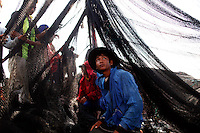 Migrant workers from Myanmar clean a fishing net as they sail out of port of Mahachai near Bangkok February 23, 2010. Migrant workers in Thailand face extortion, arbitrary detention, forced  labour and physical abuse, sometimes at the hand of authorities amid a pervasive  climate of impunity, a leading rights group said on Tuesday.   REUTERS/Damir Sagolj (THAILAND)