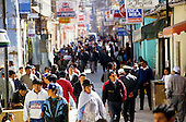 Puno, Peru. Men and women wearing traditional and modern clothes on a busy street; many shop signs; policeman.