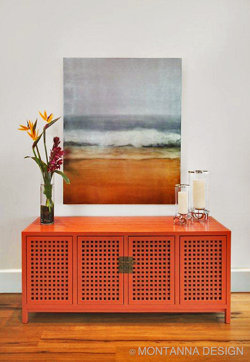 Chinese lacquered orange credenza at modern interior.