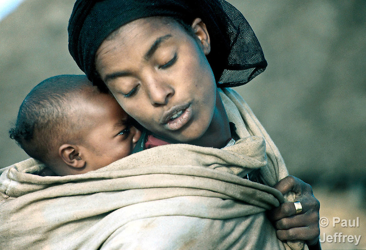 A woman soothes her hungry child in Gubalaftu, a village in the North Welo region of Ethiopia, during a 2000 famine..