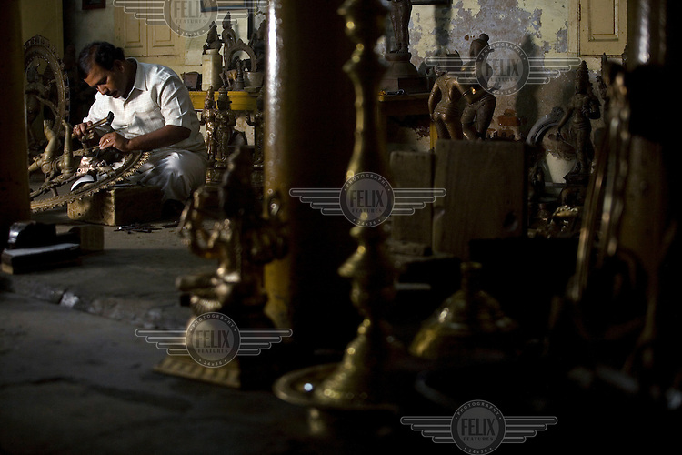 Master craftsman Radhakhrishna Sthapathy works on the final touches to a statue of the dancing Nataraja at dawn in the S. Devasenapathy Sthapathy and Sons bronze casting workshop. The current Sthapathy generation is the twenty-third generation of bronze casters. Their method using the lost-wax process remains unchanged to this day.