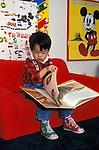 "Berkeley CA Four-year-old boy (Chinese American) ""reading"" dinosaur book in bedroom  MR"