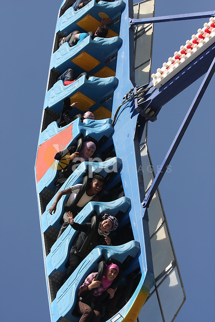 Palestinians enjoy a ride in an amusement park in the West Bank city of Ramallah on the second day of Eid al-Adha,on, November, 17, 2010. as Muslims worldwide commemorate Eid al-Adha, or the Feast of the Sacrifice, marking the end of the hajj and commemorating Abraham's willingness to sacrifice his son Ismail on God's command. Photo by Issam Rimawi
