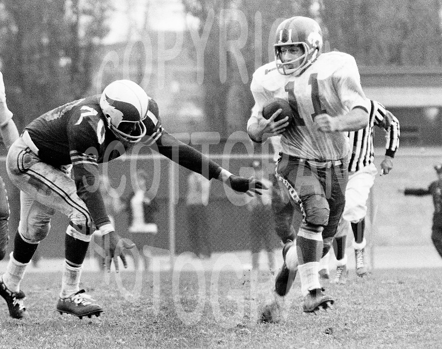 Ron Stewart Ottawa Rough Riders is chased by Montreal Alouettes player Russ Buckle 1963. Copyright photograph Ted Grant