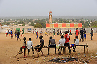 SIERRA LEONE , youngster play football infront of mosque